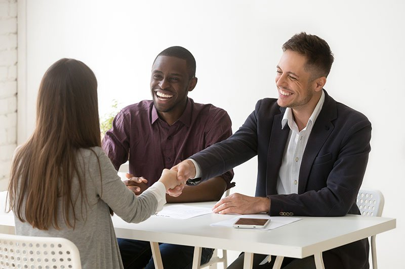 two men smiling and shaking hands with woman sitting at table